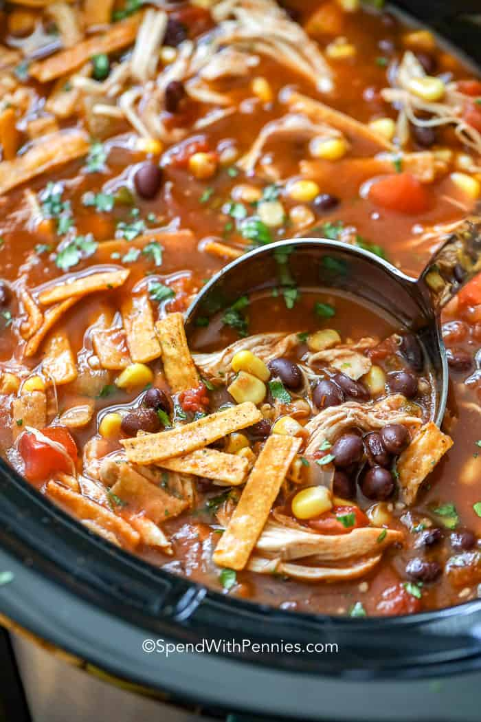 Slow cooker tortilla soup being ladled out of a Crock Pot.