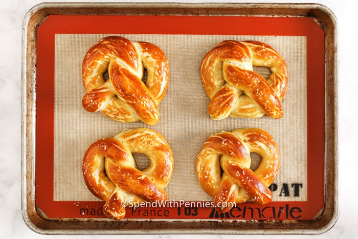 Four baked soft pretzels on a baking tray.