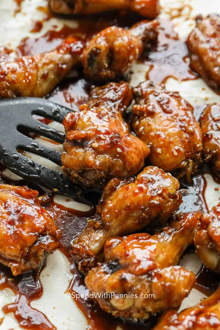 Honey garlic chicken wings being served from a baking sheet fresh from the oven.