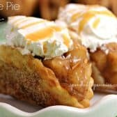 two apple pie tacos topped with whipped cream and caramel on a white plate