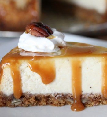 side view of a slice of banana cheesecake topped with whipped cream and pecans