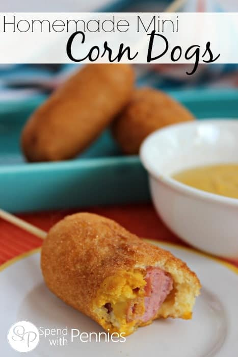 mini corndog on a plate with dip and more corndogs in the background