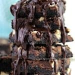 close up of a stack of Death By Chocolate Magic Cookie Bars topped with fudge sauce
