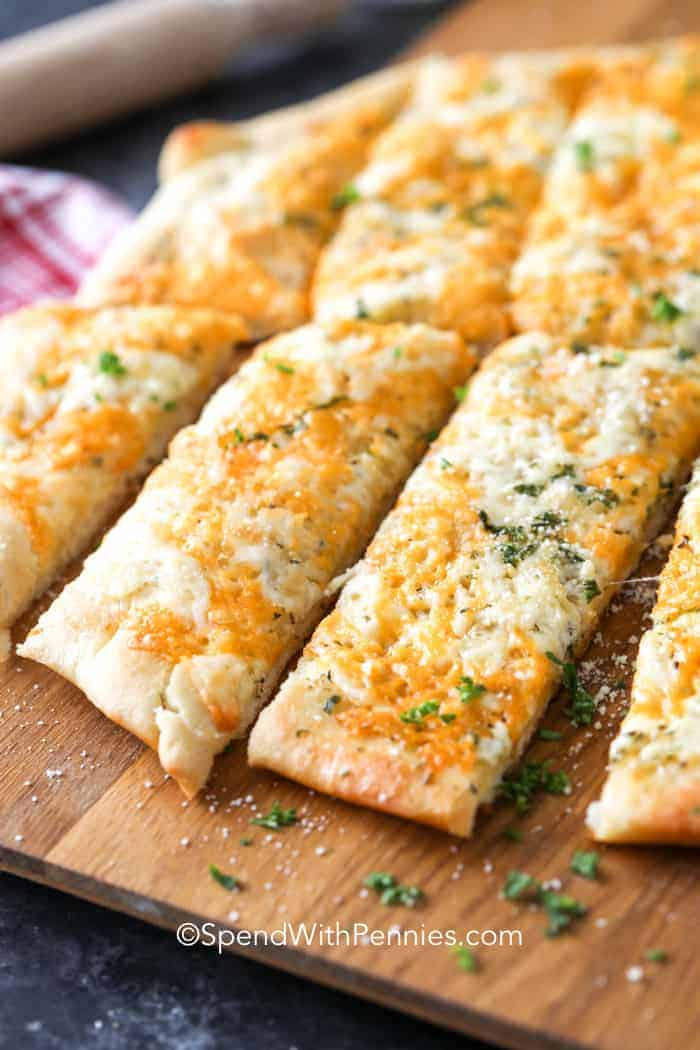 Cheesy breadsticks cut into sticks on a cutting board, sprinkled with parsley.