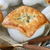 Chicken pot pie in a white dish on a baking sheet with a fork and spoon