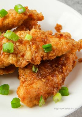 Honey Garlic Chicken Tenders on a white plate with green onion garnish