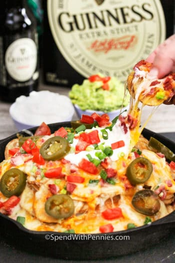 Irish Pub Style Nachos with someone taking nachos