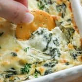 spinach and artichoke dish with cracker