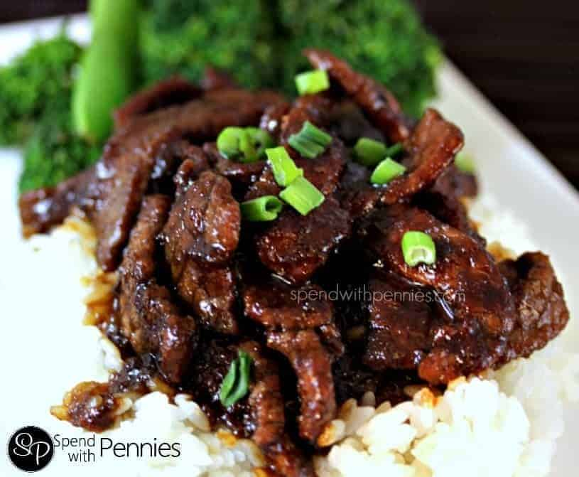 PF Changs style Mongolian beef with rice on a white plate and green onion garnish