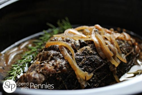 Slow Cooker Rosemary Beef Roast with onions on the top and a rosemary garnish