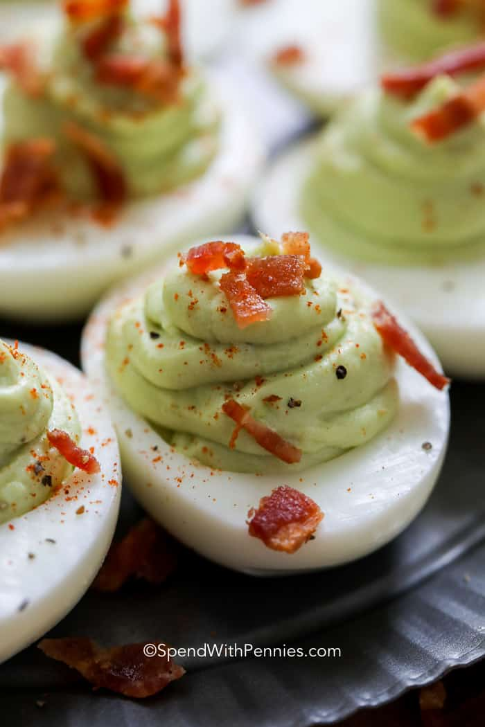 Avocado Deviled Eggs topped with bacon ready to serve.