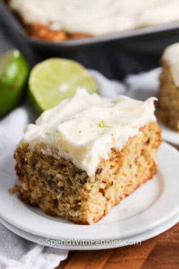 Tropical Banana Snack Cake on a white plate with the cake and lime behind it