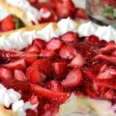 fresh strawberries and cream pie with a slice out of it with berries in the background