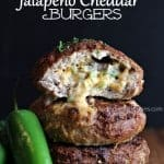 a stack of Jalapeno Cheddar Burgers with cheese oozing out and a jalapeño on the side
