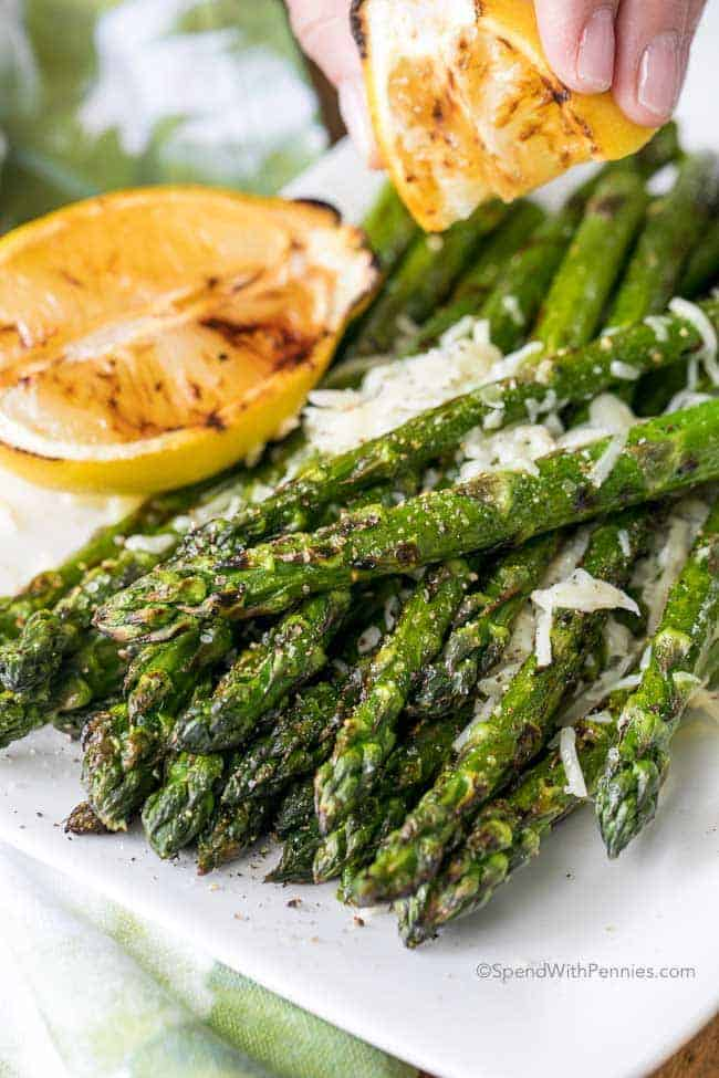 Lemon Parmesan Grilled Asparagus on a white plate topped with cheese