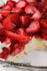 close up of fresh strawberries and cream pie with a slice out of it