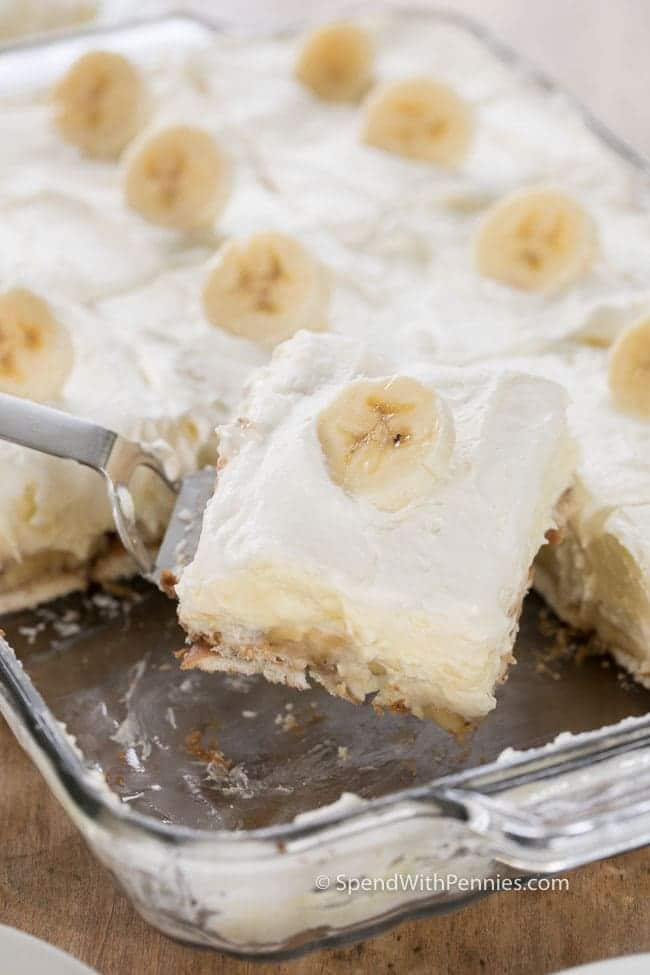 Lifting a serving of Homemade Banana Pudding out of a baking dish with a spatula