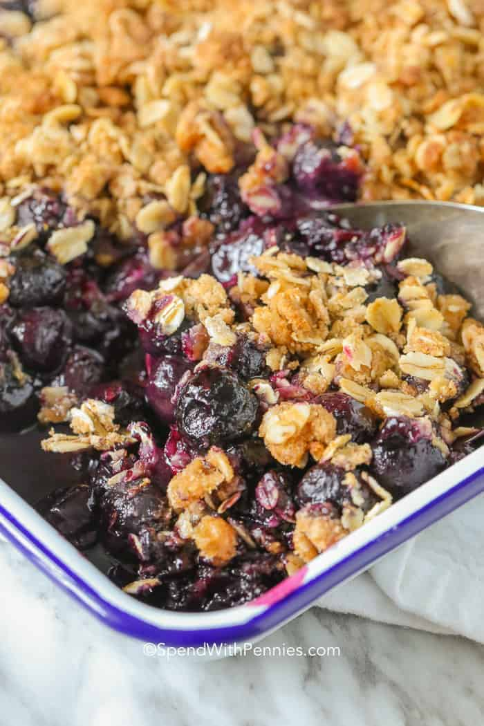 Blueberry Crisp served with a spoon from a baking dish