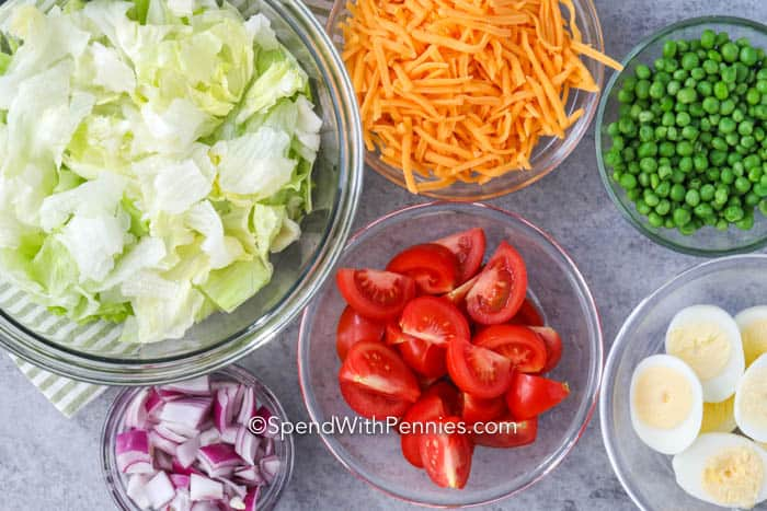 Ingredients for the perfect layered salad in bowls on a marble board