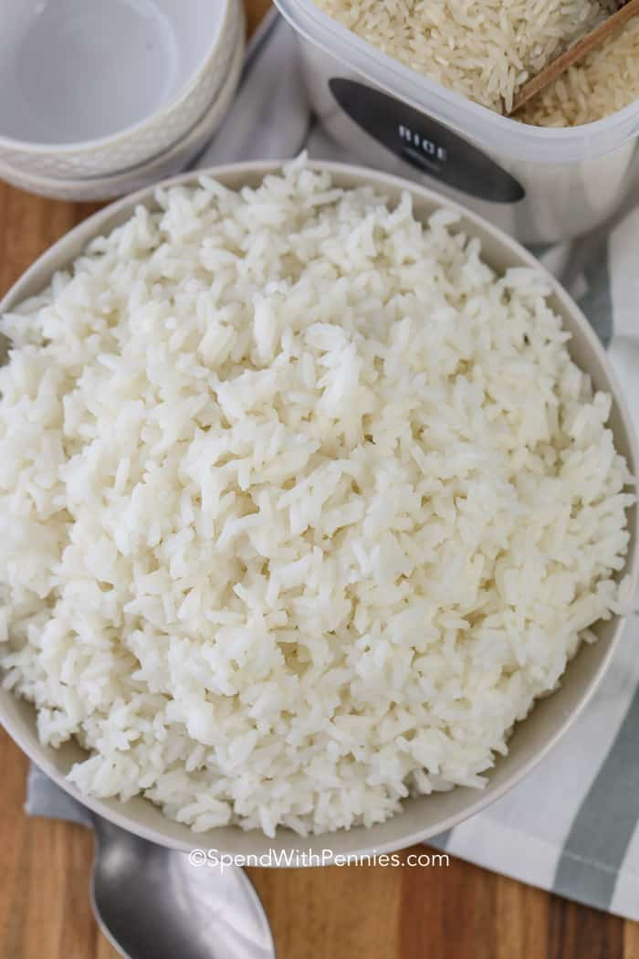 An overhead shot of a bowl of fluffy white rice with a spoon.