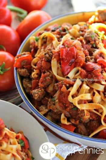 Sausage & Roasted Pepper Linguine in a bowl with tomatoes in the background