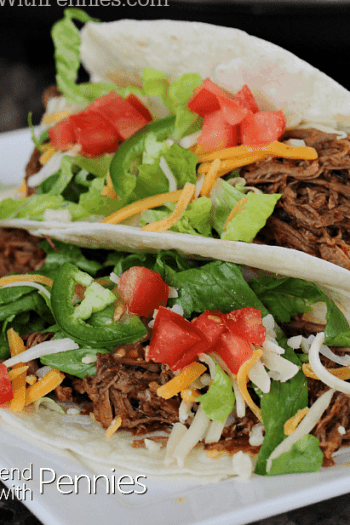 close up of two soft shelled tacos filled with shredded beef and vegetables