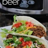 two soft shelled tacos filled with shredded beef and vegetables with a slow cooker in the background