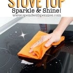 Wiping a black stovetop with an orange cloth. Here are some great tips to clean a stove top and make is sparkle and shine like new!