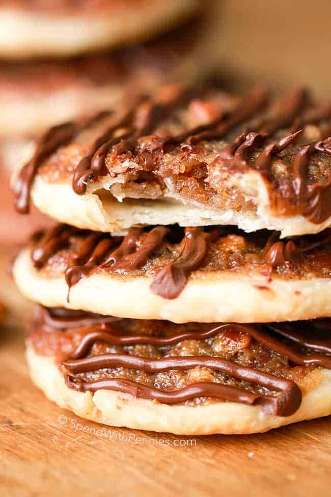A stack of three pecan pie cookies topped with chocolate with a bite