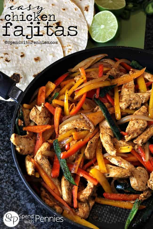 Chicken fajitas in a cast iron pan with tortillas and lime.