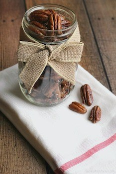 glazed pecans in a jar with a bow