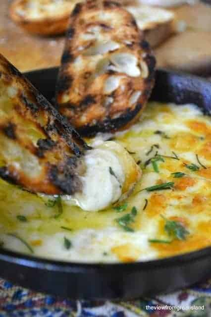 cheesy dip in a small skillet with charred crostini