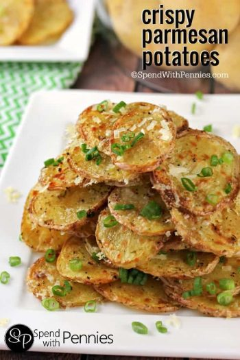 a pile of crispy Parmesan Potatoes garnished with green onions on a plate