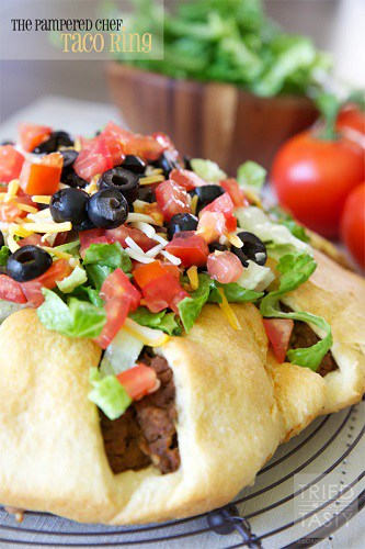 taco ring mad with crescent rolls topped with tomatoes, lettuce and olives