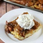 Apple Pie French Toast Casserole with whipping cream on a white plate with the casserole in the background