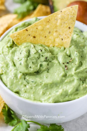 White bowl of Avocado Dip and Dressing with a chip in it