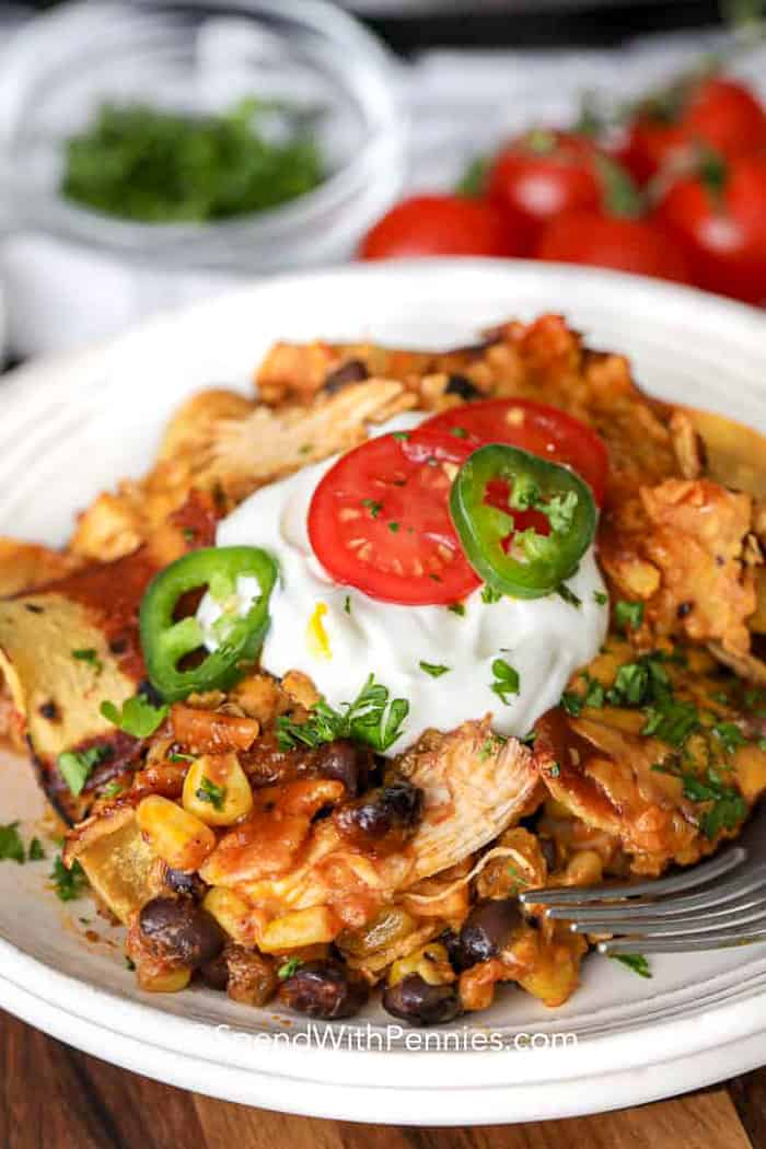 Slow cooker enchiladas on a plate topped with sour cream, tomatoes and jalapenos
