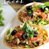Two crockpot chicken tacos on white plate