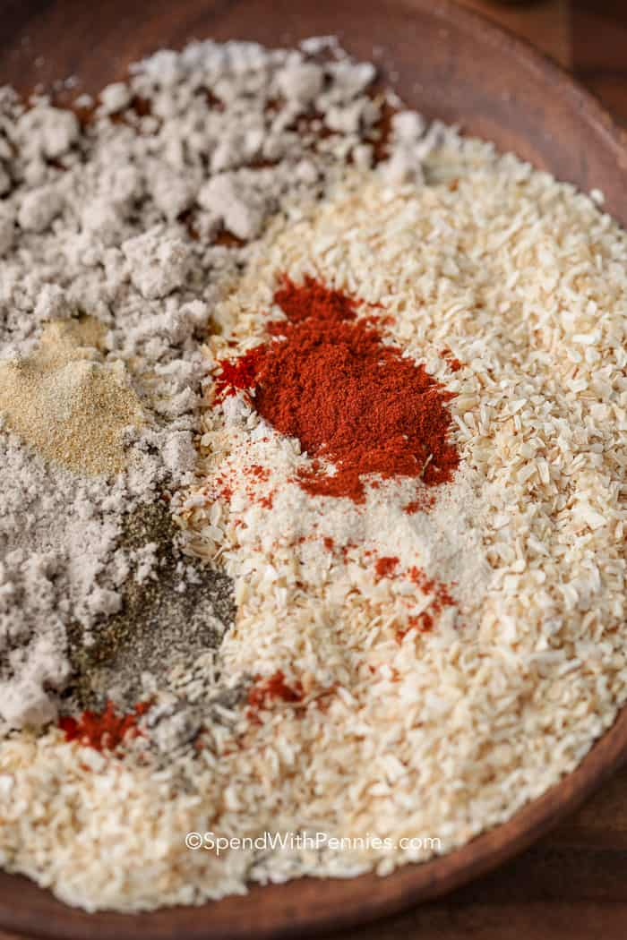 Spices for homemade onion soup mix in a wooden mixing bowl including onion flakes, bouillon, and paprika.