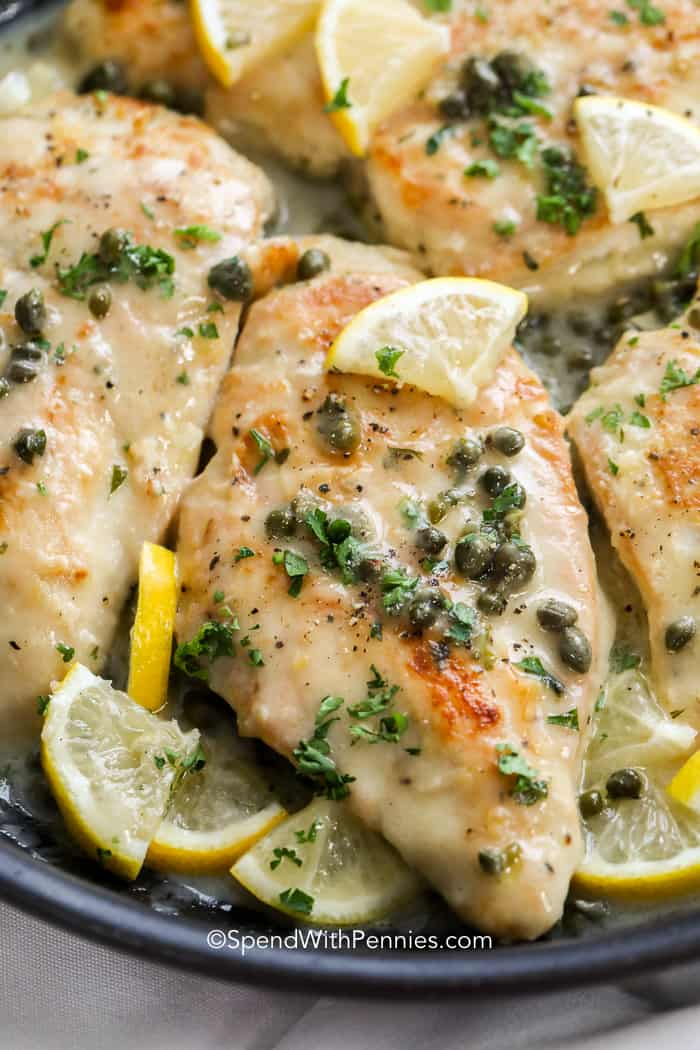 chicken piccata sauce poured over searched chicken with lemon and capers