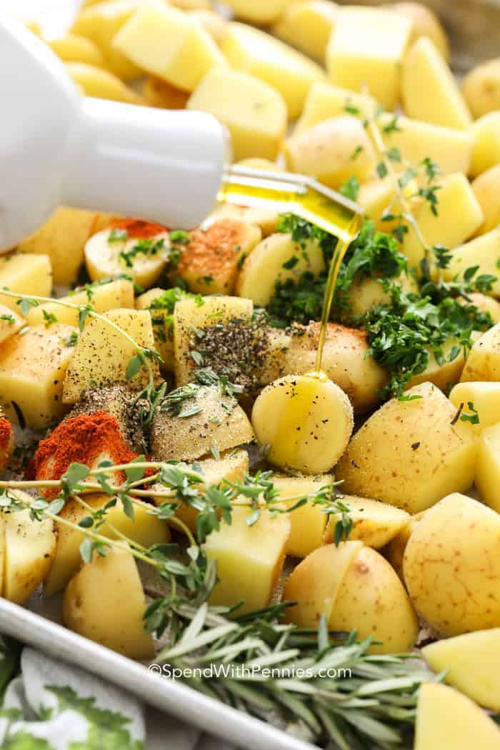 Adding fresh herbs, spices and olive oil to potatoes for the perfect oven roasted potatoes recipe