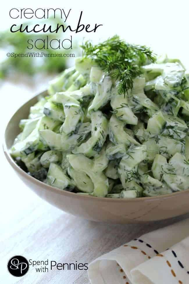 A bowl of creamy cucumber salad on a cutting board.