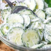 Creamy Cucumber Salad in a mixing bowl being stirred with a spoon