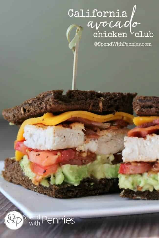 California Avocado Chicken Club Sandwich on pumpernickel bread on a white plate with a bamboo spear