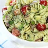 avocado pasta salad with tomatoes in a white bowl
