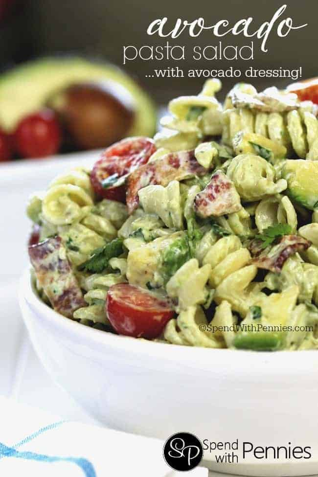 side view of avocado pasta salad with tomatoes in a white bowl