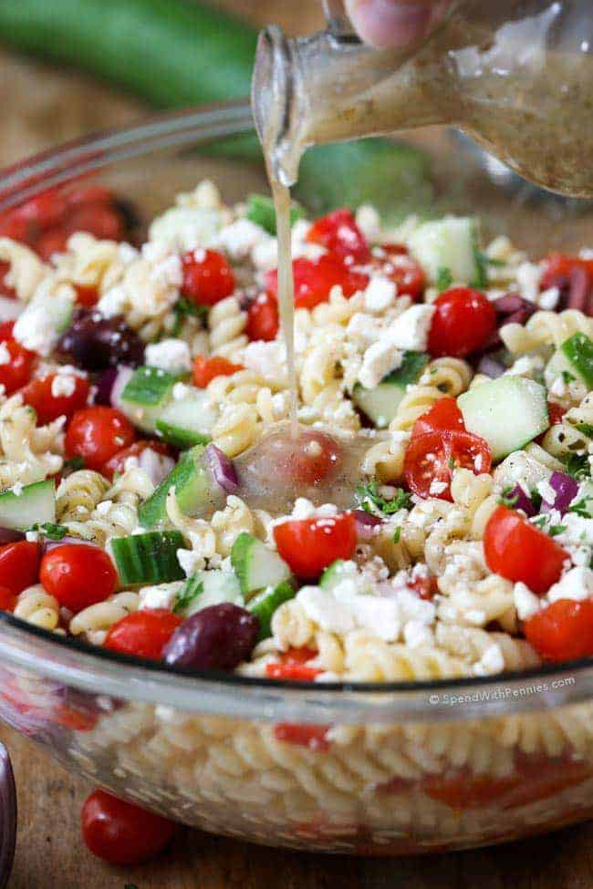 Greek Pasta Salad with dressing being poured on