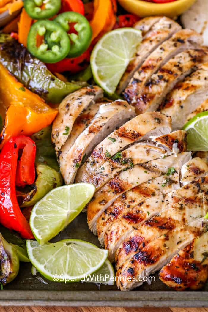 Ingredients for grilled chicken fajitas on a baking sheet with lime wedges