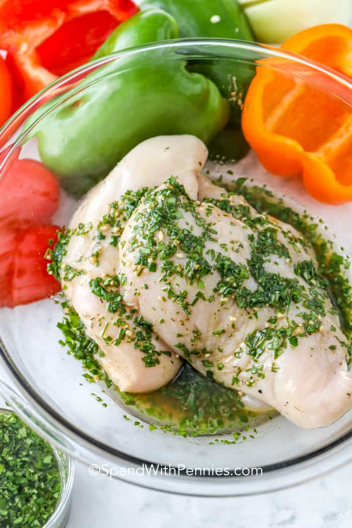 Raw chicken breast with marinade in a glass bowl for chicken fajitas