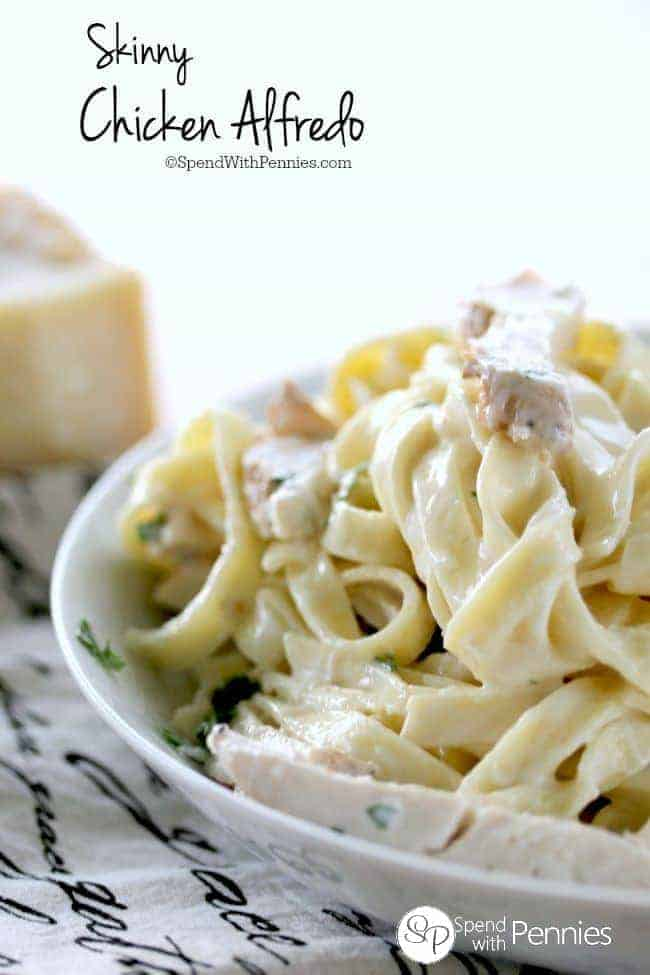 Skinny Chicken Alfredo in a bowl next to a block of parmesan